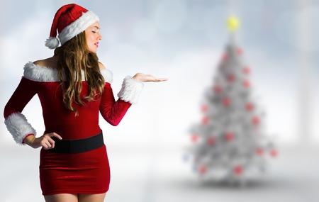 pere noel sexy: Jolie fille en costume de Santa tenue main contre l'arbre de No�l floue dans la chambre