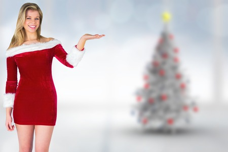 Pretty girl presenting in santa outfit against blurry christmas tree in room