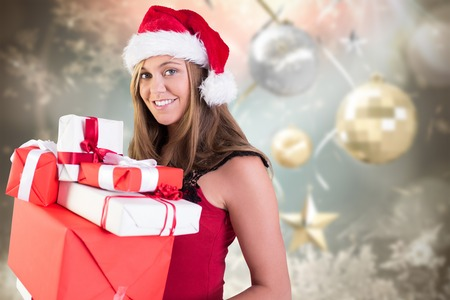 Festive blonde holding pile of gifts against blurred christmas background photo