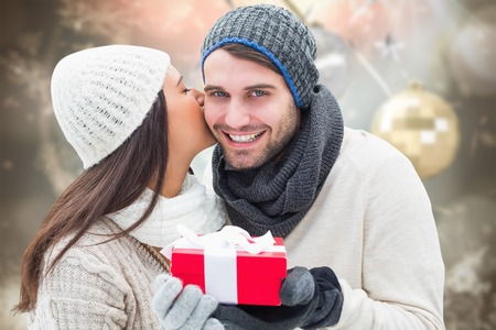 Winter couple holding gift against blurred christmas background Stock Photo