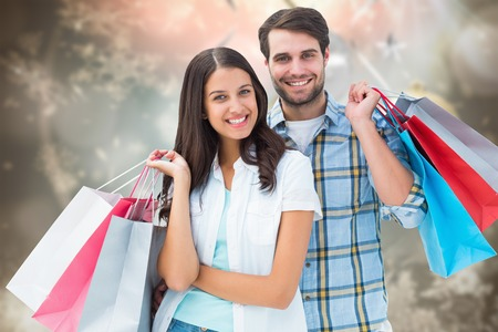 Happy couple with shopping bags against blurred christmas background photo