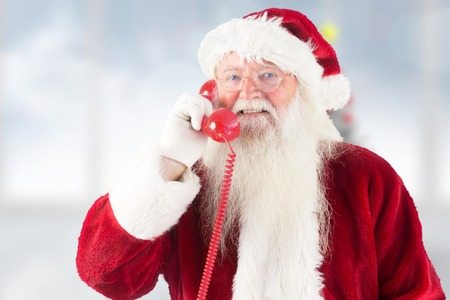 Santa claus on the phone against blurry christmas tree in room photo