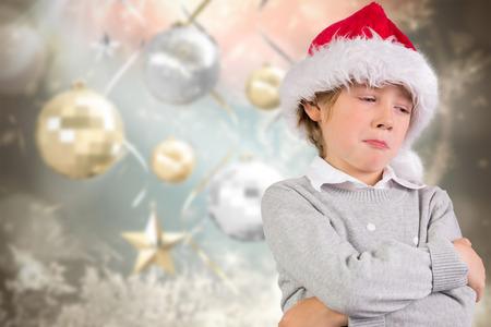 sulking: Festive boy sulking against blurred christmas background