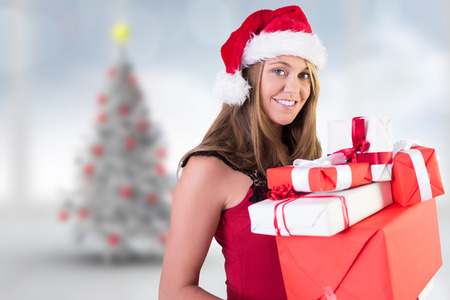 Festive blonde holding pile of gifts against blurry christmas tree in room photo