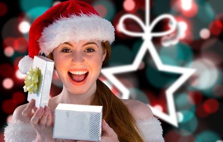 pere noel sexy: Sexy girl en costume de Santa ouverture d'un cadeau de No�l sur fond flou