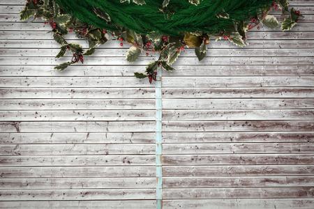 Festive christmas wreath against digitally generated grey wooden planks photo