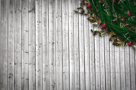 Festive christmas wreath with decorations against digitally generated grey wooden planks photo