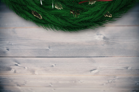 Festive christmas wreath against bleached wooden planks background photo