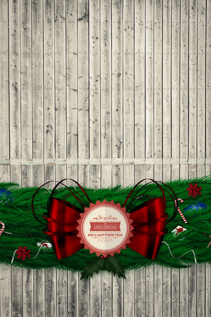 Fir branch christmas decoration garland  against digitally generated grey wooden planks photo