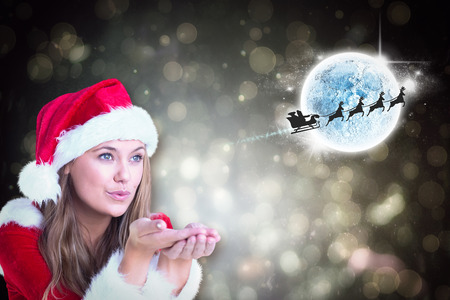 Festive blonde blowing over hands against black abstract light spot design photo
