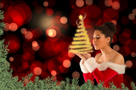 Pretty santa girl blowing over her hands against green fir branches photo