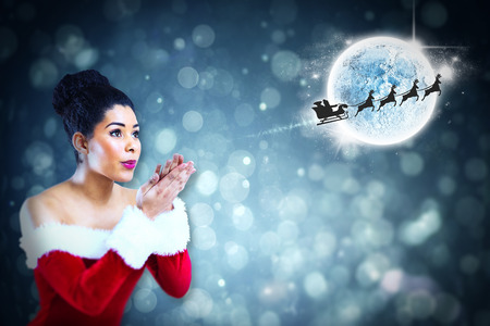 Pretty santa girl blowing over her hands against santa and his sleigh flying photo