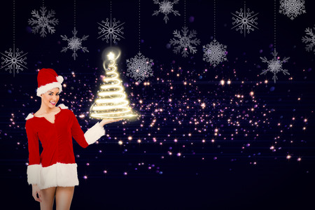 Pretty santa girl presenting with hand against hanging snowflakes photo