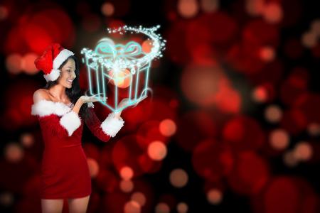 pere noel sexy: Jolie fille pr�sentant � santa tenue contre cadeau de No�l rougeoyant Banque d'images