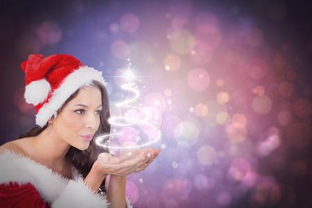 pere noel sexy: Jolie fille � santa tenue soufflant contre la conception de l'arbre de No�l Banque d'images