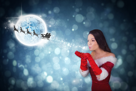 Pretty girl in santa outfit blowing against santa and his sleigh flying photo