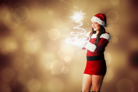 pere noel sexy: Jolie fille en costume de Santa tenue main contre la conception abstraite de point lumineux d'orange