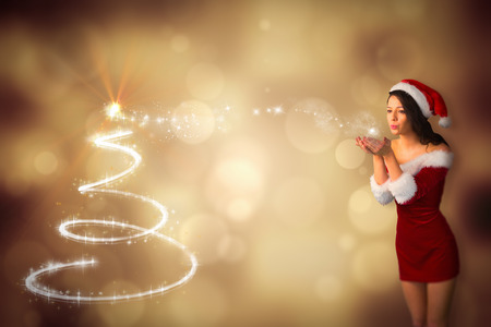 Pretty girl in santa outfit blowing against christmas tree design photo