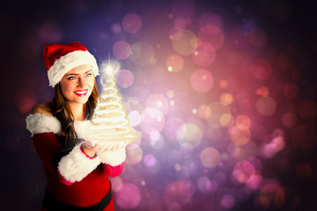 Pretty girl in santa costume holding hand out against purple abstract light spot design photo
