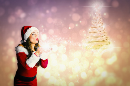Pretty girl in santa costume holding hand out against pink abstract light spot design photo