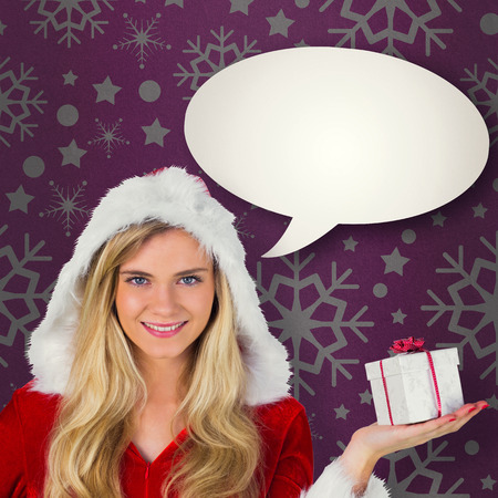 Pretty girl in santa outfit holding gift against pink vignette photo