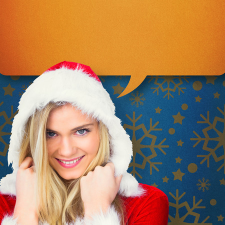 Pretty girl smiling in santa outfit against blue vignette photo