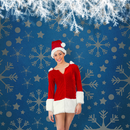 Pretty santa girl smiling at camera against blue vignette photo