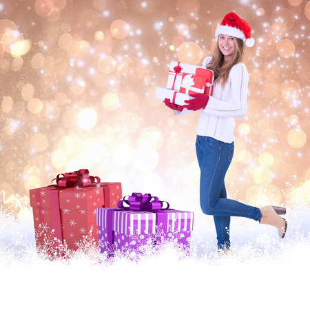 Festive blonde holding pile of gifts against yellow abstract light spot design photo