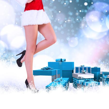 pere noel sexy: womans Festive jambes en hauts talons contre des points brillants de lumière sur le bleu
