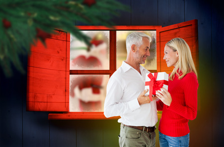 Loving couple with gift against festive fir branch with baubles photo