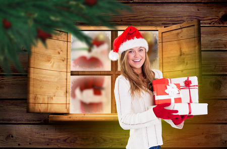 Festive blonde holding pile of gifts against festive fir branch with baubles photo