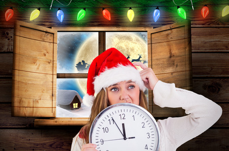 Festive blonde showing a clock against santa delivery presents to village photo