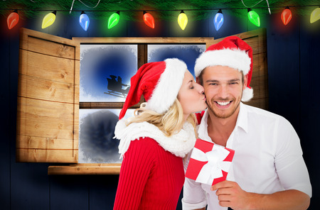 Young festive couple against santa delivery presents to village photo