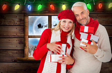 Happy festive couple with gifts against santa delivery presents to village photo