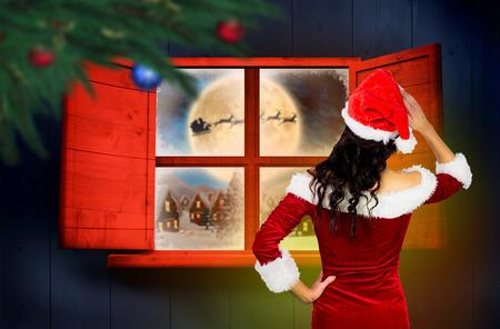 sexy santa girl: Rear view of sexy santa girl against santa delivery presents to village Stock Photo