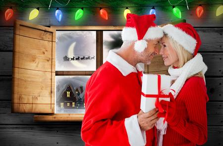 Festive couple against santa delivery presents to village photo