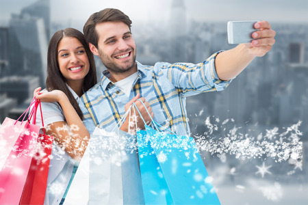 Happy couple taking a selfie against room with large window looking on city photo