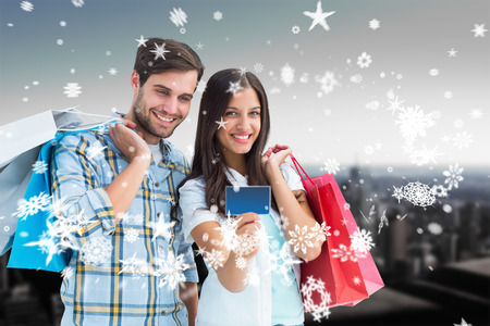 Couple with shopping bags and credit card against high angle view of city skyline photo