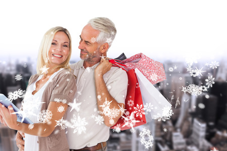Happy couple with shopping bags and tablet pc against high angle view of city photo