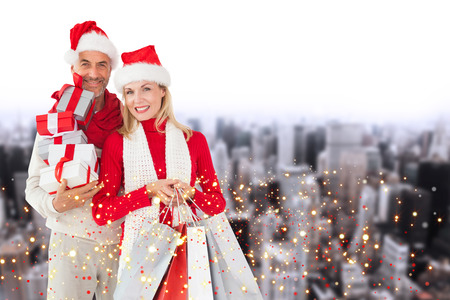Happy festive couple with gifts and bags against high angle view of city photo