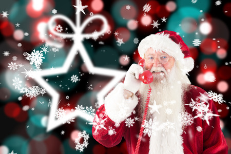 Santa claus on the phone against blurred christmas background photo