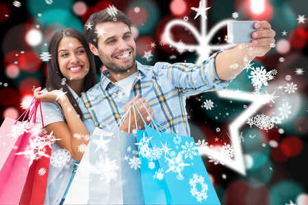 Happy couple taking a selfie against blurred christmas background photo