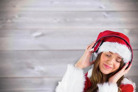 pere noel sexy: Sexy santa girl �couter de la musique contre les planches de bois floues