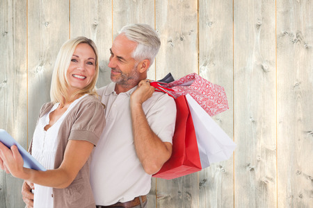 Happy couple with shopping bags and tablet pc against pale wooden planks photo
