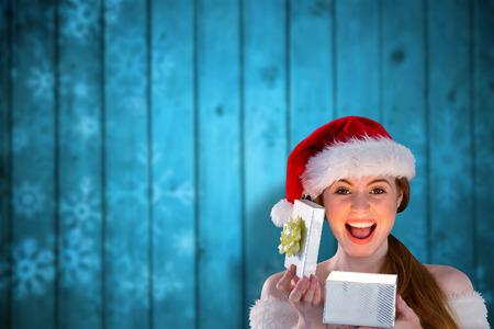 pere noel sexy: Sexy girl en costume de Santa ouverture d'un cadeau contre des flocons de neige sur les planches floues