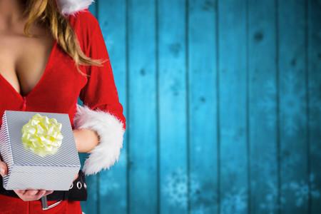 sexy santa girl: Sexy santa girl holding gift against blurred snowflakes on planks Stock Photo