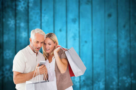 Happy couple with shopping bags and smartphone against blurred snowflakes on planks photo