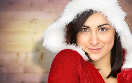 pere noel sexy: Jolie jeune fille souriante � santa tenue contre planches de bois floues Banque d'images