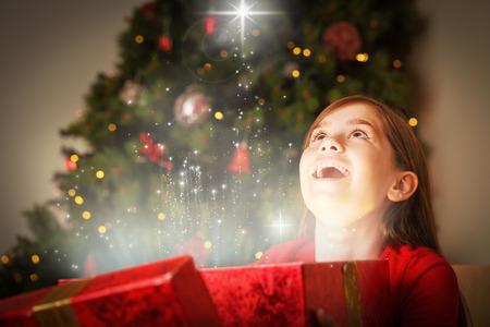 女の子が雪に対して魔法のクリスマスのギフトを開く