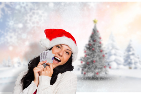 woman holding money: Woman holding money towards herself against blurry christmas scene